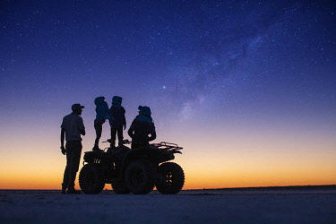 BOT5878 Camp Kalahari, Makgadikgadi, Botswana, a guide and guests look at the night sky from a quad bike on the salt pans.