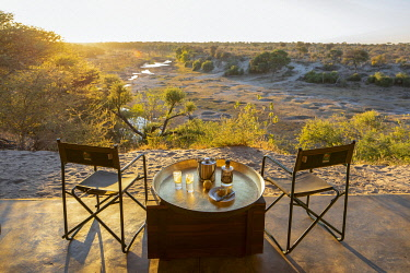 BOT5946 Botswana; Makgadikgadi; Meno a Kwena, a table and chairs set with sundowners before a stunning river bed view at sunset.