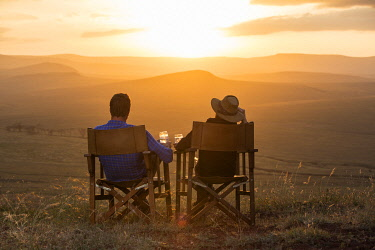 KEN11558 Sirikoi, Lewa Wildlife Conservancy, Kenya, a couple enjoy sundowners before a stunning sunset.