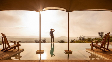 KEN11613 Elewana Loisaba Lodo Springs, Kenya, a man looks out from the edge of the infinity pool.