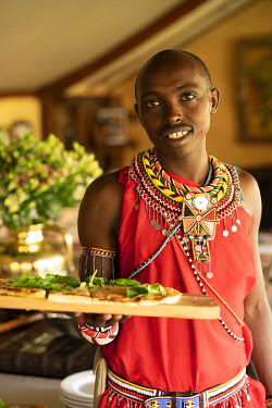 Enasoit, Laikipia, Kenya, a waiter holds a board with fresh pizza for lunch.
