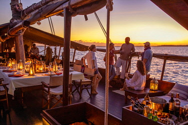 Tusitiri Dhow, Lamu Archipelago, Kenya, a group of friends chat at sun set over sundowners.