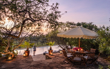 Campi ya Kanzi, Chyulu Hills, Kenya, a table set for super next to the swimming pool in camp.