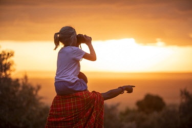KEN11768 House in the Wild, Masai Mara, Kenya, a little girl sits on a guides shoulders and looks through binoculars.