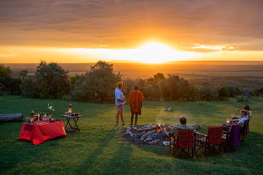 KEN11785 House in the Wild, Masai Mara, Kenya, enjoying sundowners around a camp fire at sunset.
