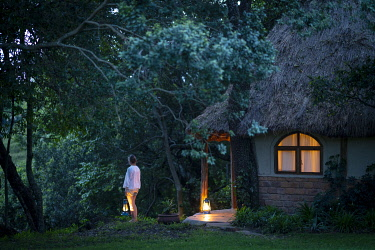 KEN11806 House in the Wild, Masai Mara, Kenya, a woman holds a lantern outside a guest cottage at dusk.