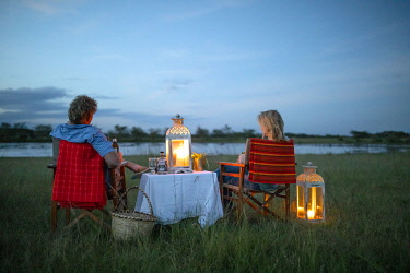 House in the Wild, Masai Mara, Kenya, a couple enjoy sumdowners at dusk by a hippo pool.