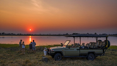 BOT6020AW People having sundowners on safari, Moremi National Park, Okavango Delta, Botswana