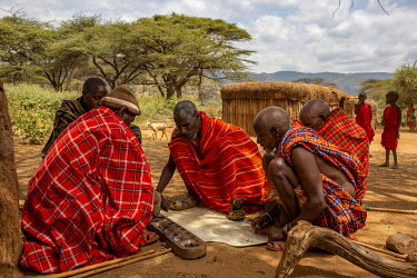 KEN11903 Kenya, Laikipia County,Il Ngwesi village, Samburu men play mancala.