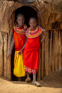Kenya, Laikipia County, Il Ngwesi village, children stand in the doorway of a traditional house.