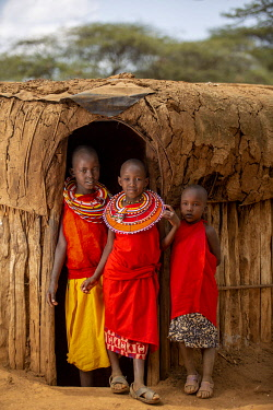KEN11913 Kenya, Laikipia County, Il Ngwesi village, children stand in the doorway of a traditional house.