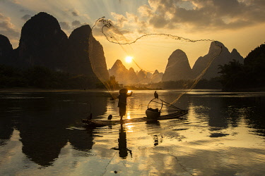 CH12542AW Cormorant fisherman throwing net on Li River at dawn, Xingping, Yangshuo, Guangxi, China