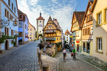 Cyclists on Spitalgasse street with Plonlein half-timbered building and Siebers Tower, Rothenburg ob der Tauber, Bavaria, Germany