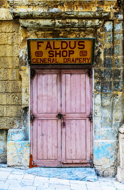 MLT0849 Maltese Islands. Malta. Southern Europe. Old Door with a shop sign dating back to the British rule on the islands and facade in the Baroque Capital City of Valletta.