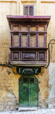 MLT0850 Maltese Islands. Malta. Southern Europe. Old Door with a shop sign dating back to the British rule and traditional Maltese balcony on a facade in the Baroque Capital City of Valletta.