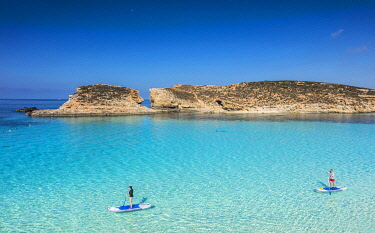 MLT0865 Maltese Islands. Malta. Southern Europe. Stand up paddle boarding on the island of Comino s famed bay blue lagoon with its bright blue waters. It has served as a backdrop to several Hollywood producti...