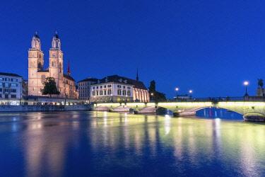 CLKRM118917 Limmatquai, Grossmunster Cathedral and Munsterbrucke bridge at dusk, Zurich, Switzerland