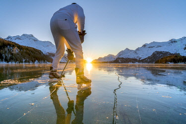 CLKRM137427 Rear view of ice hockey player on frozen Lake Sils at sunset, Graubunden, Engadine, Switzerland (MR)