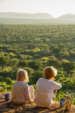 KEN12052 Tassia Lodge, Lekurruki conservancy, Kenya, children sit with hot chocolate and look out at the view.