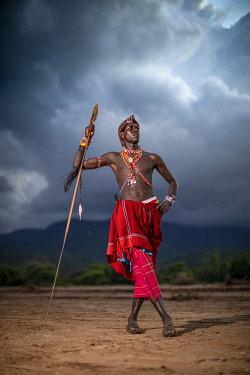 KEN12079 Tassia Lodge, Lekurruki conservancy, Kenya, a Maasai man poses with his spear before a dramatic cloudy sky.
