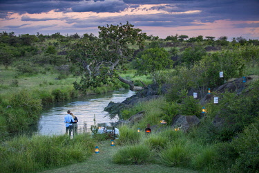 Richards Camp, Masai Mara, Kenya, a couple enjoy the scenary beside the river in the evening at a bush dinner.