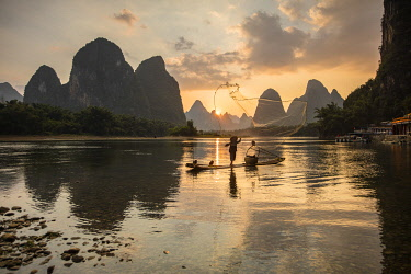 CH12555AW Cormorant fisherman throwing net on Li River at dawn, Xingping, Yangshuo, Guangxi, China