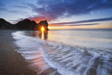 Sun shining through Durdle Door at sunrise, Jurassic Coast, Dorset, England, UK