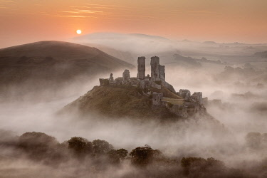 ENG18565AW Corfe Castle at dawn surrounded by mist, Dorset, England