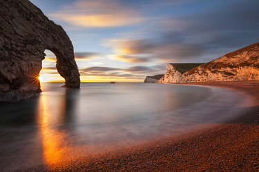 ENG18663AW Sun setting through Durdle Door, Jurassic Coast, Dorset, England, UK