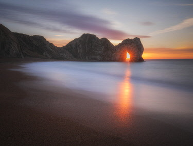 ENG18735AW Sunrise through Durdle Door, Jurassic Coast, Dorset, England, UK