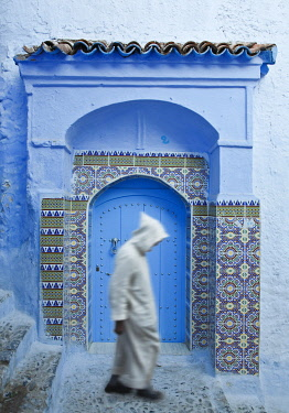 Man in Burnoose walking past blue doorway, Chefchaouen, Morocco