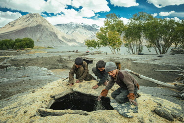 IBLFBA06031980 Three boys shovel wheat grains through the opening from above into a granary, members of the ethnic group of the sedentary Wakhi, Saradh-e-Broghil, Wakhan Corridor, Afghanistan, Asia