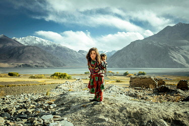 IBLFBA06032375 Girl carrying her little brother on her back, members of the ethnic group of sedentary Wakhi, Saradh-e-Broghil, Wakhan Corridor, Afghanistan, Asia