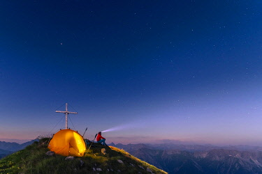 IBXSEI05915042 Cross of the Kreuzspitze by a starry sky with tent and mountaineer at the summit, in the background the Lechtal Alps, Elmen, Lechtal Alps, Außerfern, Tyrol, Austria, Europe