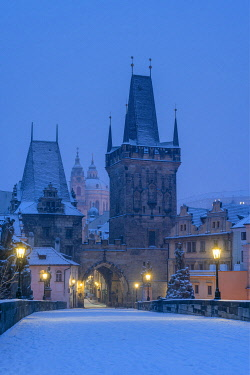 CZE2524AW Mala Strana Bridge Tower at snow-covered Charles Bridge at twilight in winter, Prague, Bohemia, Czech Republic