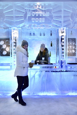 Sweden, Lapland, Norrbotten County, Jukkasjärvi, warmly dressed young woman and barmaid at the counter of the blue-lit bar of the Ice Hotel, the first ice hotel to be built in the world