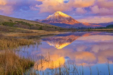 Ireland, Co.Donegal, Snow capped Errigal mountain reflected in Clady river at dusk