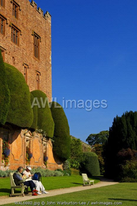 Wales; Powys; Welshpool. A couple of visitors relax on a bench enjoying the view from the Top Terrace in the spectacular garden at  Powis Castle