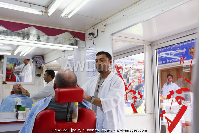 Oman, Dhofar. A visitor to Salalah has a close shave in a typical barber's shop. (MR)