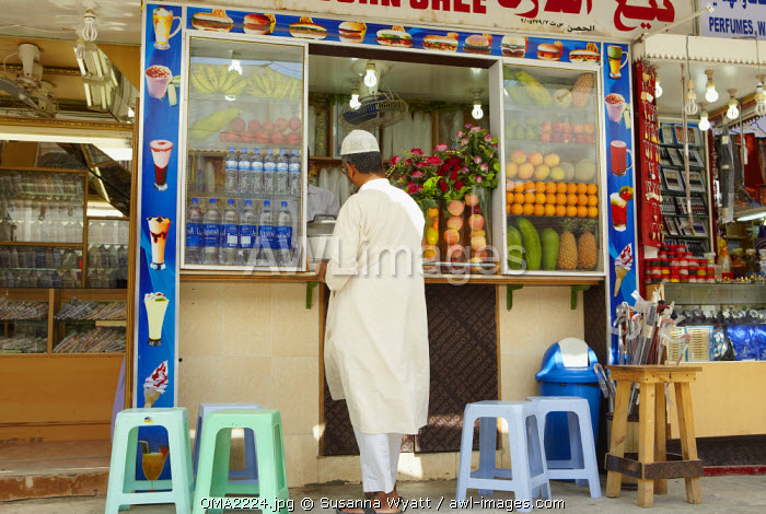 Oman, Dhofar. A passerby stops for refreshment at one of the juice bars in Salalah.