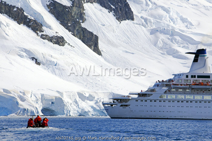 Antarctica, Antarctic Peninsula.   A zodaic with passengers returns to an expedition cruise ship anchored in Paradise Harbour.