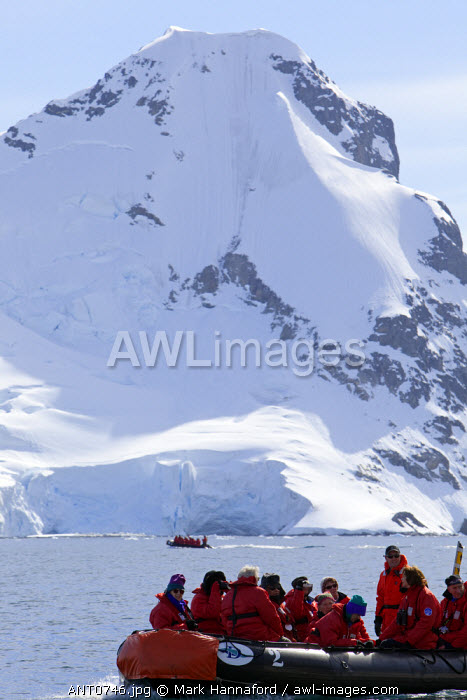 Antarctica, Antarctic Peninsula. An group of passengers dressed for operations in Antarctic waters passes underneath a heavily glaciated peak with a second zodiac in the background.