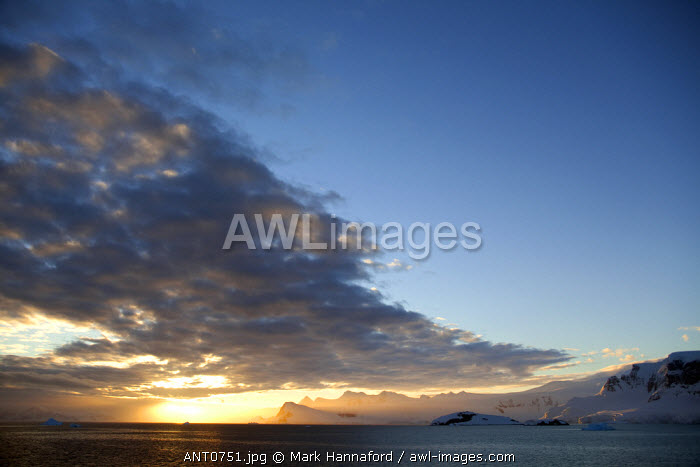 Antarctica, Peninsula.   Sunset over the Antarctic Peninsula with the clouds of a cold front being occluded by an area of high pressure.