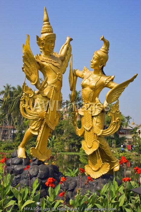 Myanmar, Burma, Yangon. A statue of the mythical creatures Kannari and Kannara - half human, half bird - in the middle of Myananda Lake.