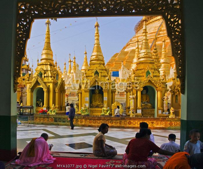 Myanmar, Burma, Yangon. Devout Buddhists pray at the small stupas, temples, shrines, prayer halls, and pavilions at the Shwedagon Golden Temple.