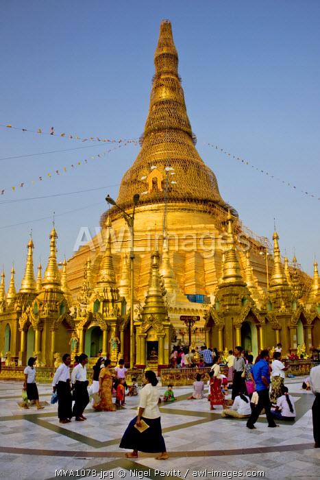 Myanmar, Burma, Yangon. Devout Buddhists at the small stupas, temples, shrines, prayer halls, and pavilions at the Shwedagon Golden Temple.
