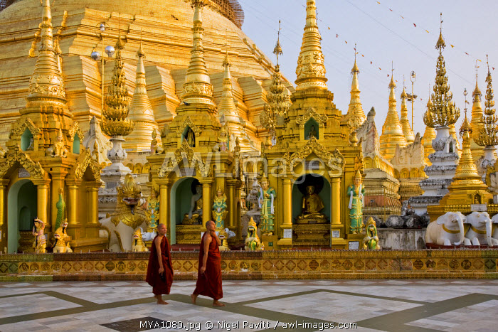 awl-images.com - Myanmar / Myanmar, Burma, Yangon. In late afternoon, two Buddhist monks pass an array of small stupas, temples and shrines at the Shwedagon Golden Temple, Myanmar's holiest site.