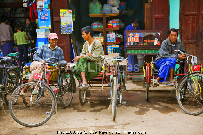 Myanmar. Burma. Nyaung U. The owners of bicycle taxis with sidecars, known as trishaws, relax as they wait for customers at Nyaung U market.