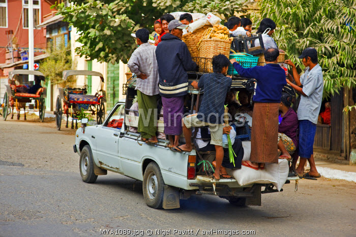 Myanmar. Burma. Nyaung U. An overloaded pick-up vehicle ferries shoppers and farmers to their distant homes from Nyaung U market.