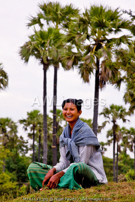 Myanmar. Burma. Bagan. A pretty girl relaxes under palm trees near Taungzin..